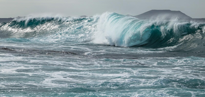 Huelga de la onda del túnel de la turquesa contra el agua poco profunda foto de archivo