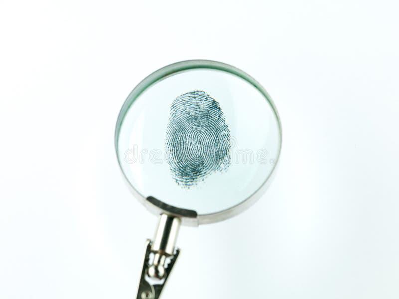 Huella dactilar a través de la lupa foto de archivo libre de regalías