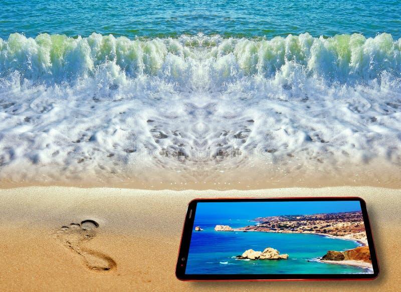 Huella en frente en la costa costa del mar y el teléfono celular azules con la pantalla que exhibe la playa del verano de Chipre foto de archivo libre de regalías