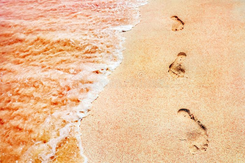 Huellas de la gente en una arena rosada de oro en las ondas suaves de la costa de mar del color rosado Cierre creativo marino del fotografía de archivo libre de regalías