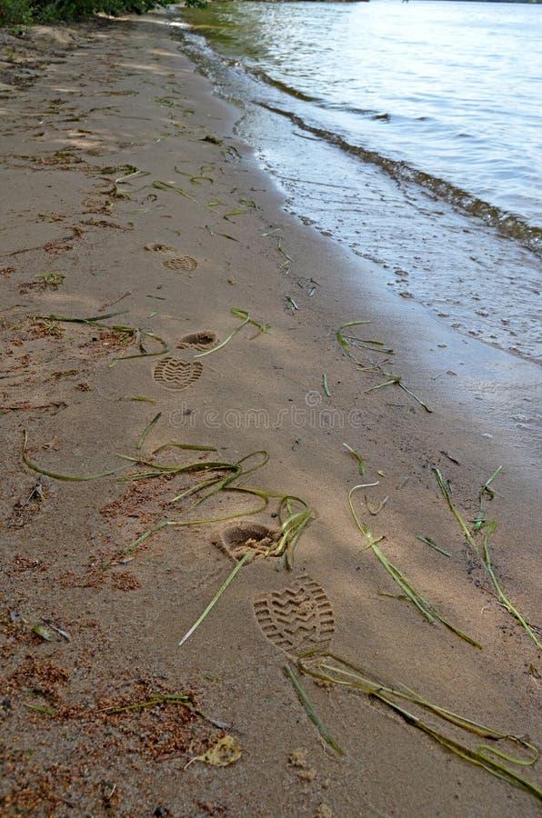 Huellas de las botas en la arena Arena mojada imagenes de archivo