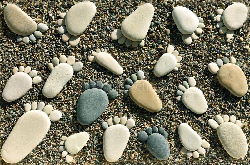 Huellas de piedras del guijarro en la arena de la playa imagenes de archivo