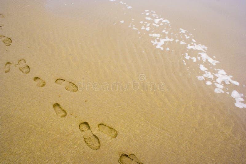 Huellas del hombre y del muchacho en la arena imagen de archivo libre de regalías