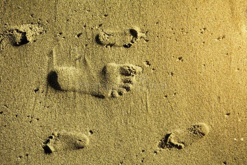 Huellas en adulto y niños de la arena fotos de archivo