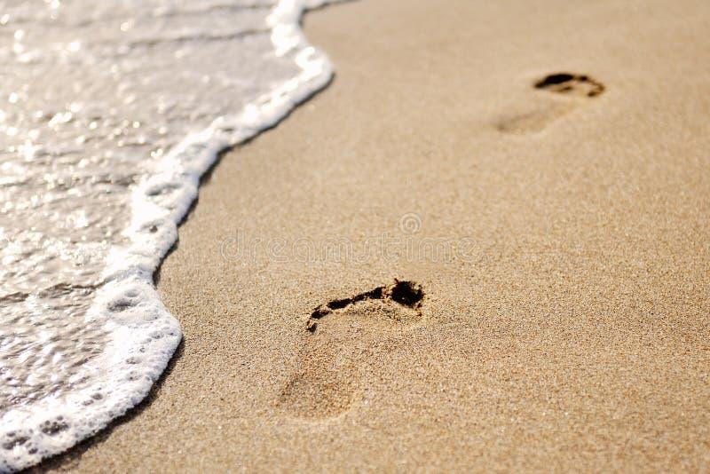 Huellas en la arena de la playa fotos de archivo