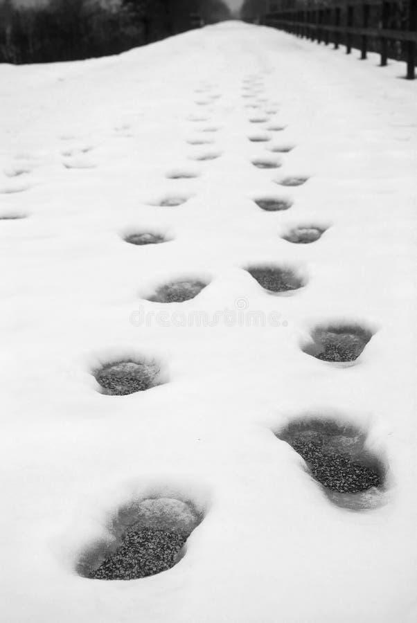 Huellas en la nieve en un camino fotografía de archivo