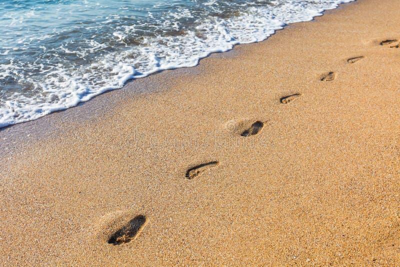 Huellas en la playa arenosa fotografía de archivo libre de regalías
