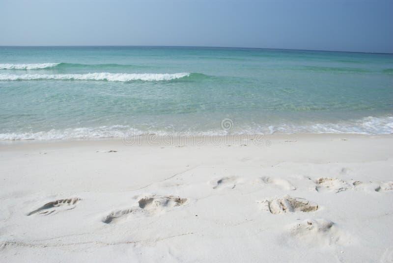 Huellas en la playa blanca de la arena imágenes de archivo libres de regalías