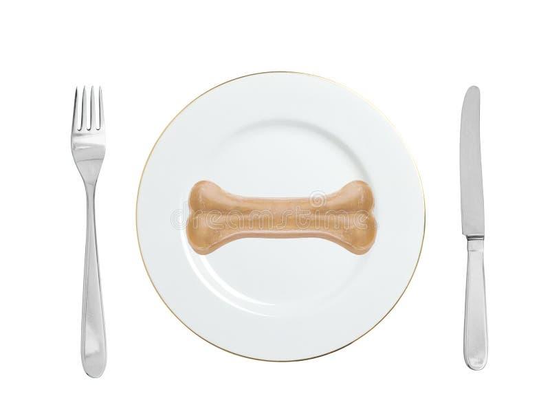 Hueso de la comida de perros en una placa con la bifurcación y el cuchillo aislado en blanco fotografía de archivo