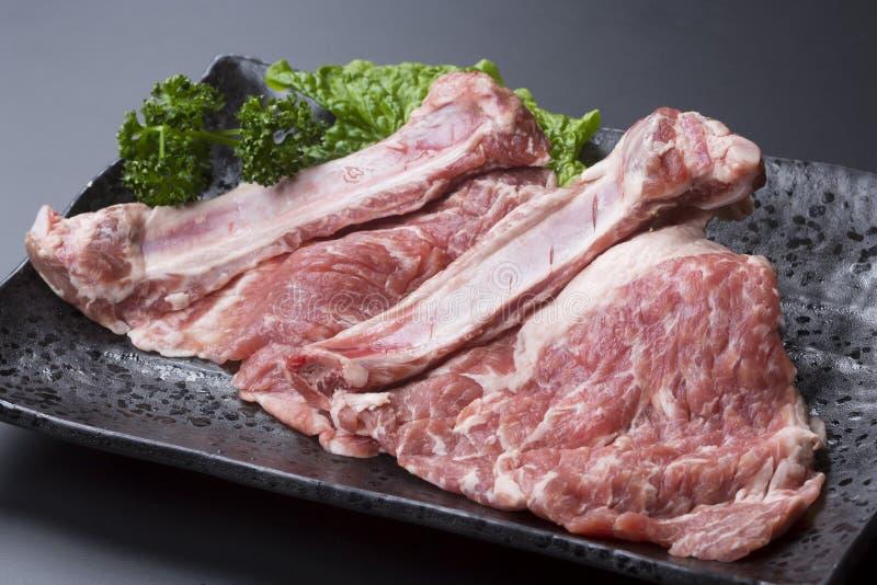 Hueso fresco en costillas de cerdo con lechuga en plato negro foto de archivo libre de regalías
