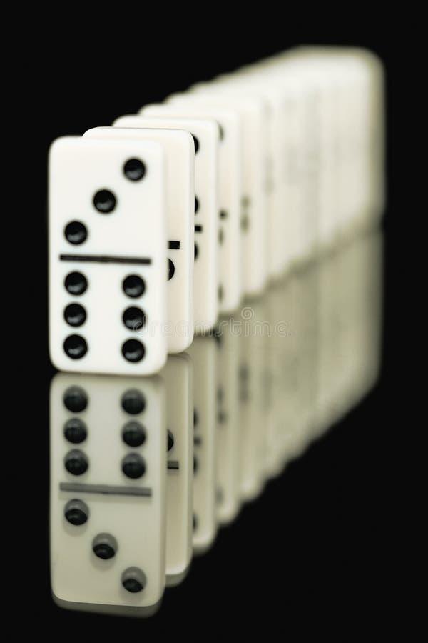 Huesos de dominós en un fondo negro imagen de archivo