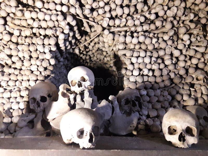 Huesos y sculls humanos colocados en un osario que es un símbolo mórbido de la muerte fotos de archivo