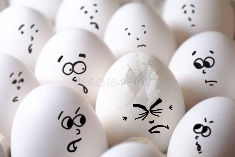 Huevo agrietado entre todos los huevos imagenes de archivo
