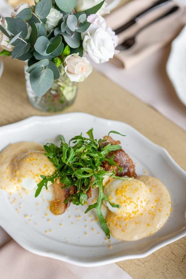 Huevo Benedicto con poca ensalada en la placa con tocino y arugula Salsa deliciosa del hollandaise de dos huevos Mañana ligera fotografía de archivo