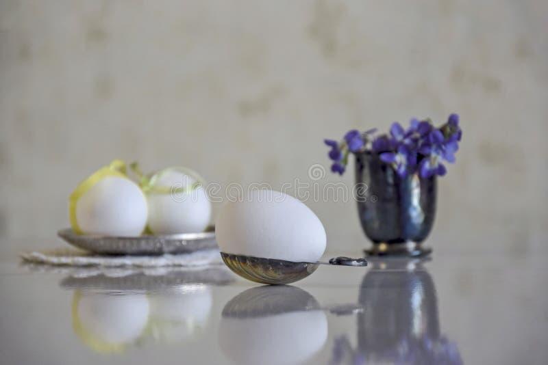 Huevo blanco en una cuchara de plata y un ramo de flores del bosque fotos de archivo libres de regalías