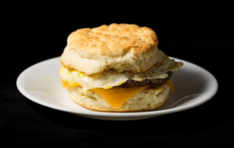 Huevo de la salchicha del desayuno y galleta del queso en un fondo negro fotografía de archivo