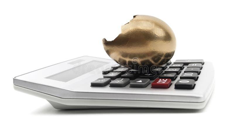 Huevo de oro agrietado en una calculadora imagenes de archivo