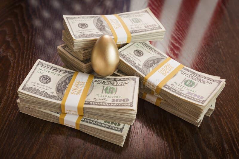 Huevo de oro y millares de dólares con la bandera americana Reflectio imagen de archivo