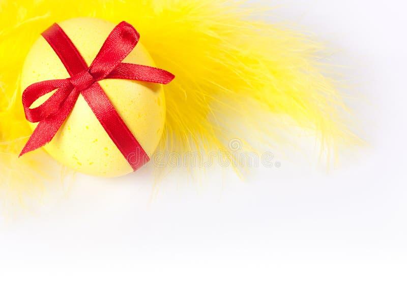 Huevo de Pascua amarillo con la pluma fotos de archivo