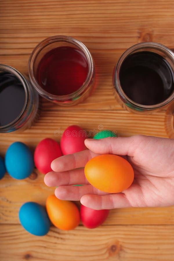 huevo de Pascua anaranjado del control de la mano de la mujer en las pinturas y el fondo coloreado de los huevos Visión superior imagenes de archivo