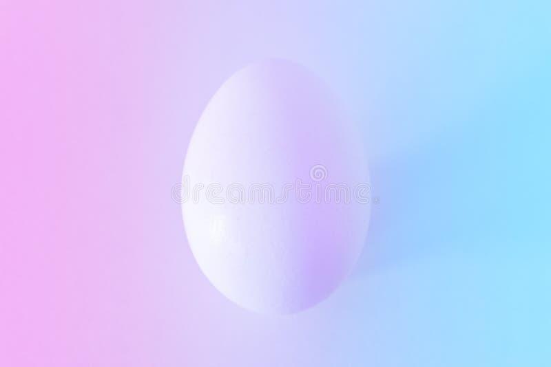 Huevo de Pascua blanco con las luces de neón ultravioletas coloridas imagenes de archivo