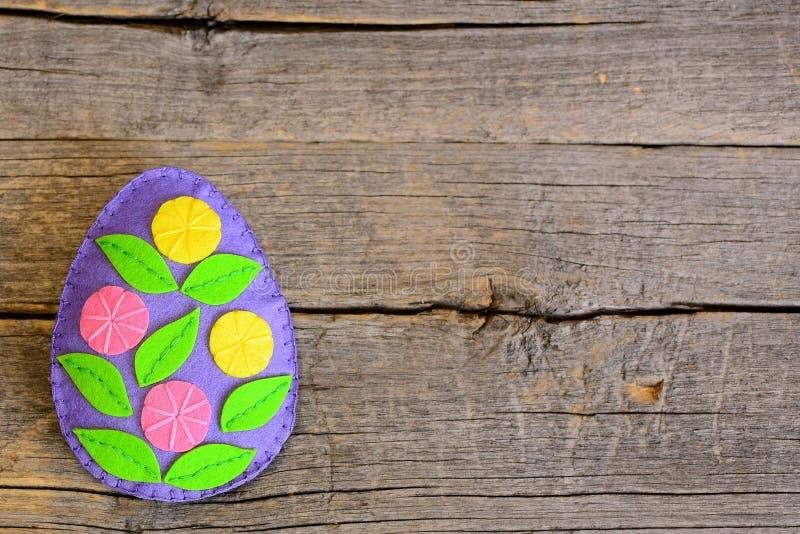Huevo de Pascua brillante del fieltro con las flores en fondo de madera con el lugar vacío para el texto fotografía de archivo libre de regalías