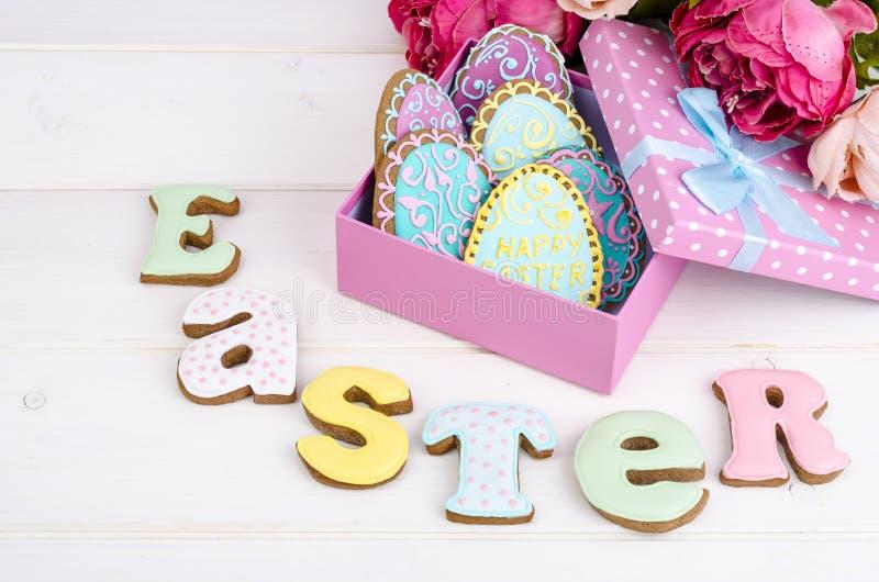 Huevo de Pascua colorido en la caja de regalo, letra Pascua de las galletas de las galletas en el fondo de madera fotos de archivo libres de regalías