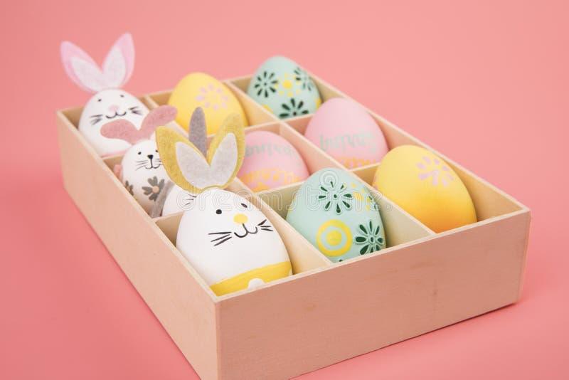 Huevo de Pascua con tema rosado en la caja el huevo se adorna como un conejito lindo que juega con otro conejito, en un fondo ros fotos de archivo