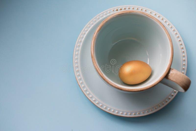 Huevo de Pascua del oro en una taza de la porcelana en un fondo azul Visi?n superior Copie el espacio fotos de archivo