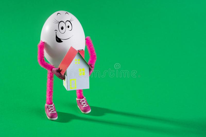 Huevo de Pascua divertido que sostiene la casa de papel miniatura imagen de archivo