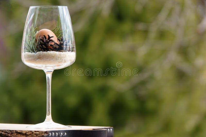 Huevo de Pascua en un vidrio adornado con los conos y la ramita naturales del pino imágenes de archivo libres de regalías