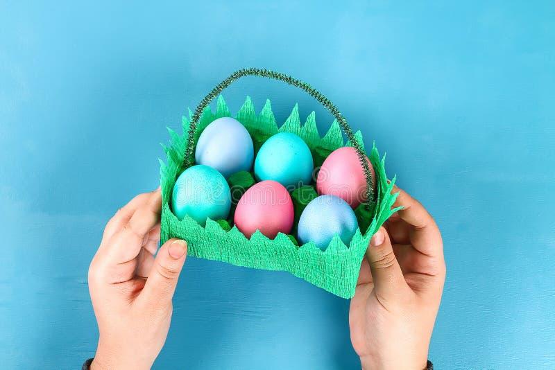 Huevo de Pascua de la cesta de DIY de la bandeja de la cartulina, papel de crespón, tronco de la felpilla en fondo azul fotos de archivo libres de regalías