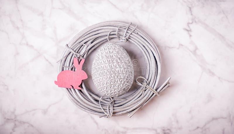Huevo de Pascua de plata y conejito rosado en la jerarquía de plata en el fondo de mármol 16:9 Concepto mínimo foto de archivo libre de regalías
