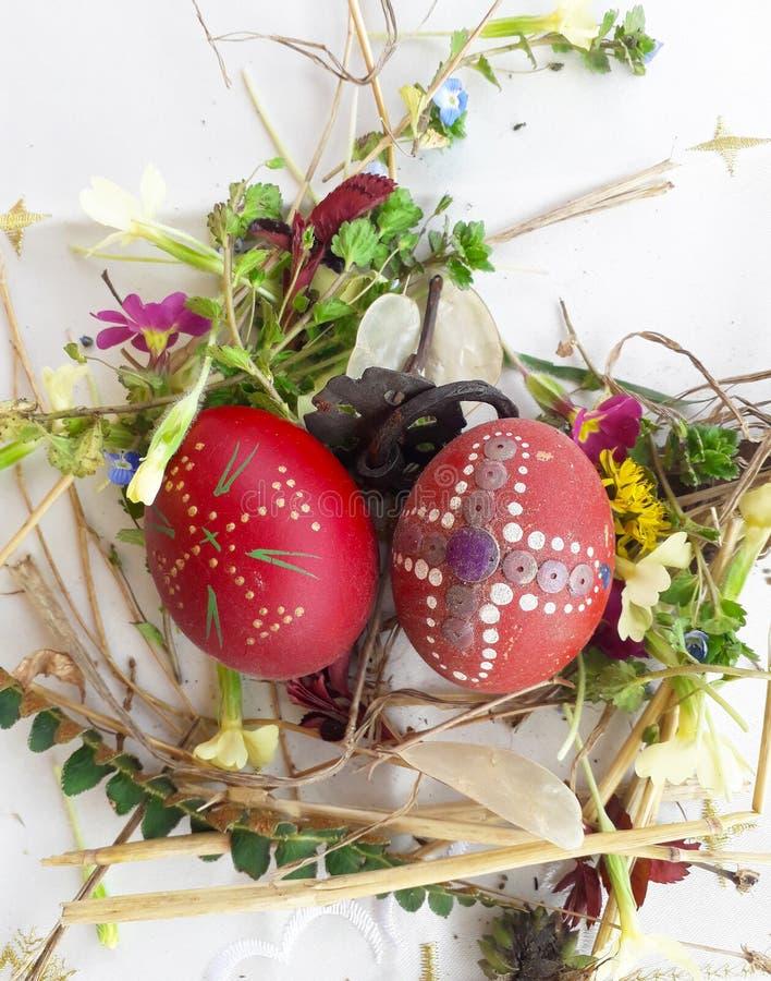 Huevo de Pascua rojo adornado con las flores salvajes y las hierbas frescas foto de archivo