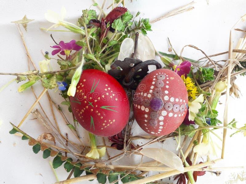 Huevo de Pascua rojo adornado con las flores salvajes y las hierbas frescas imágenes de archivo libres de regalías