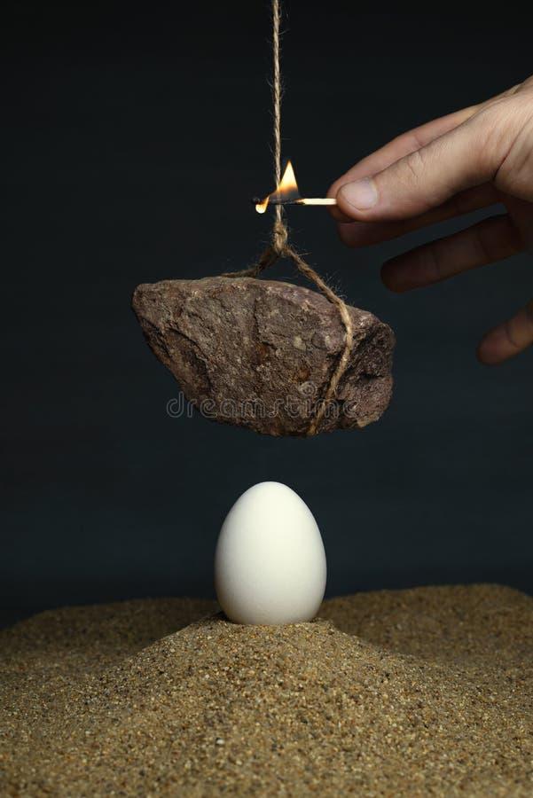 Huevo debajo de una piedra que cuelga en una cuerda fotografía de archivo libre de regalías