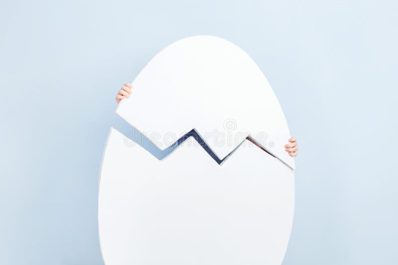 Huevo dehiscente blanco grande en el fondo de la pared azul imágenes de archivo libres de regalías