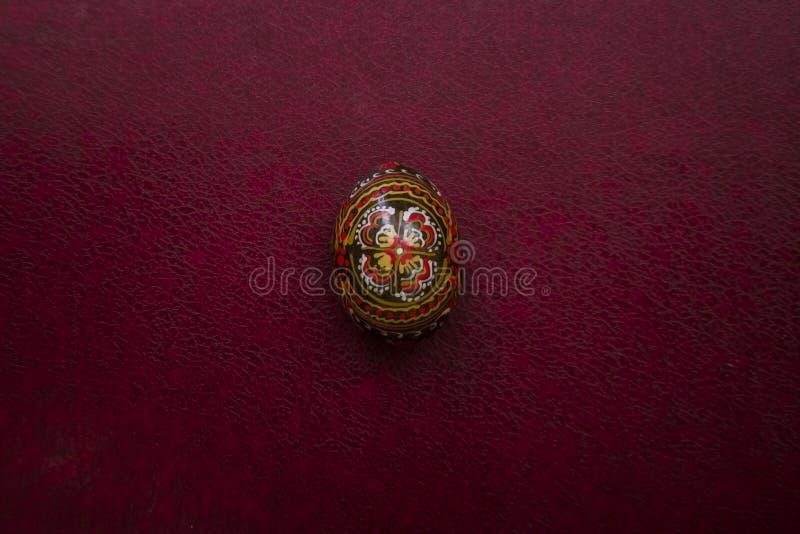 Huevo del negro de Pascua con un modelo hecho a mano Opinión del primer sobre el fondo de cuero magenta vacío, lugar para su text foto de archivo libre de regalías