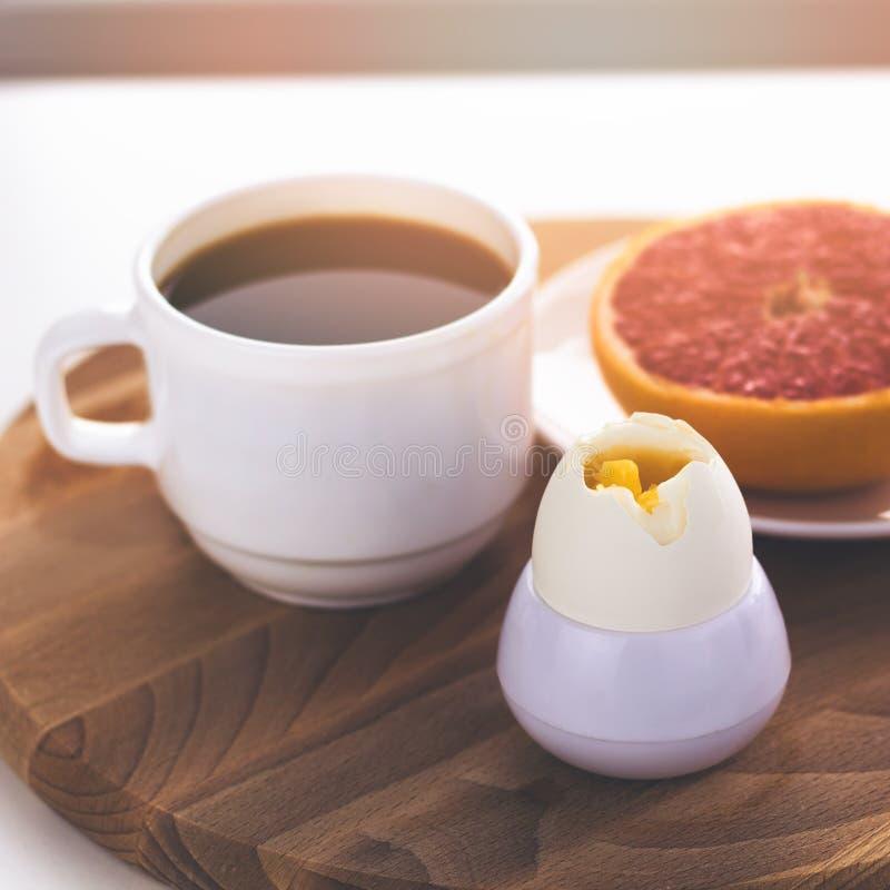 huevo duro del desayuno sano, taza de café y pomelo frescos foto de archivo