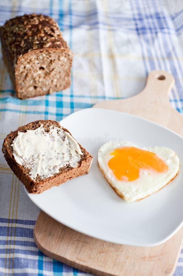 Huevo en forma de corazón en el desayuno fotografía de archivo