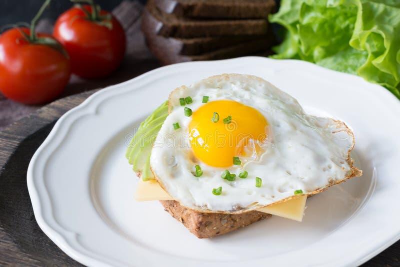Huevo frito, aguacate y queso en el pan tostado Desayuno sano en una placa foto de archivo
