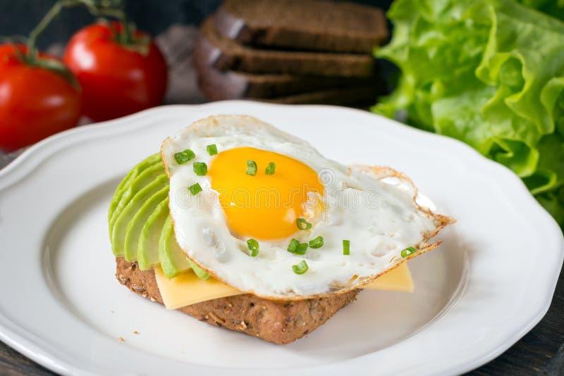 Huevo frito, aguacate y queso en el pan tostado Desayuno sano en una placa foto de archivo libre de regalías