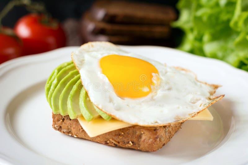 Huevo frito, aguacate y queso en el pan tostado Desayuno sano en una placa imagenes de archivo