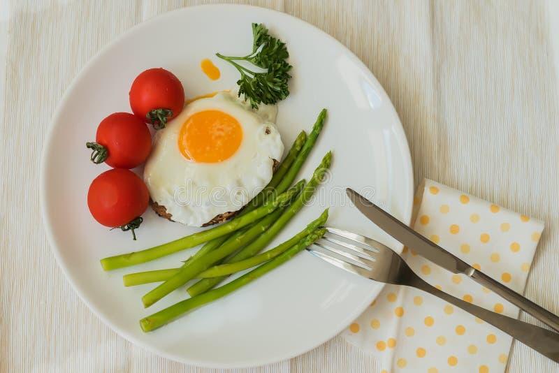 Huevo frito con el espárrago fresco, los tomates en la placa blanca con la servilleta, la bifurcación y el cuchillo Opinión super fotografía de archivo libre de regalías