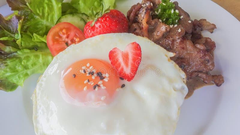 Huevo frito con el filete del cerdo de la fresa y la cena de la carne de la ensalada en plato en de madera imágenes de archivo libres de regalías