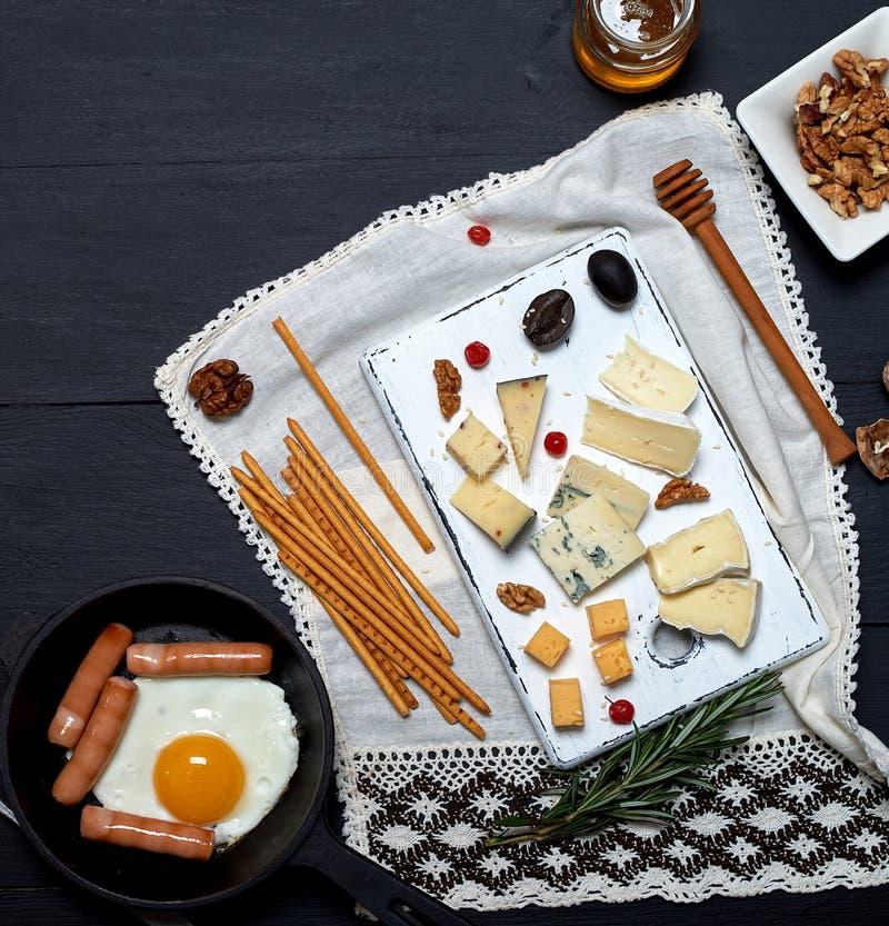huevo frito con las salchichas en un sartén redondo negro con una manija, un tablero con diverso queso cortado y una taza de café imágenes de archivo libres de regalías