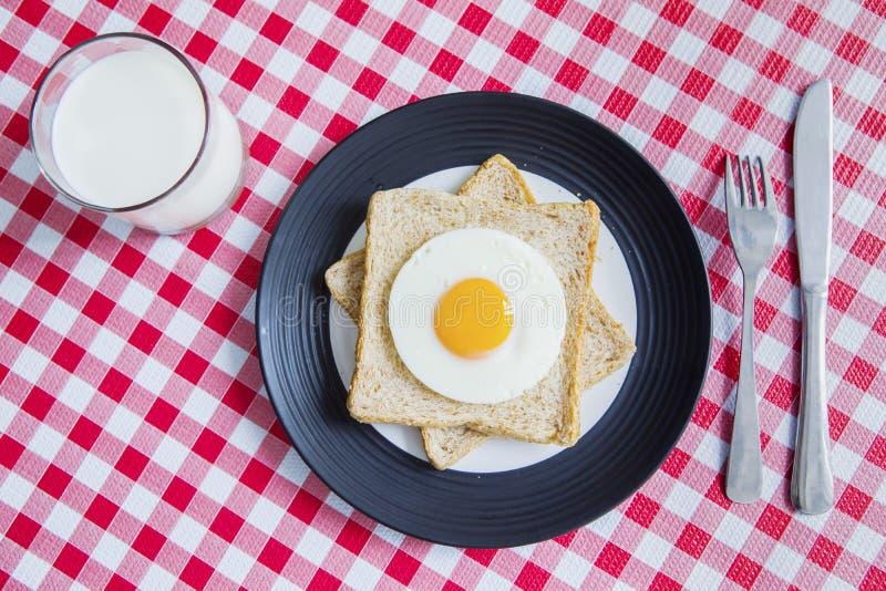 Huevo frito con pan y leche imagenes de archivo