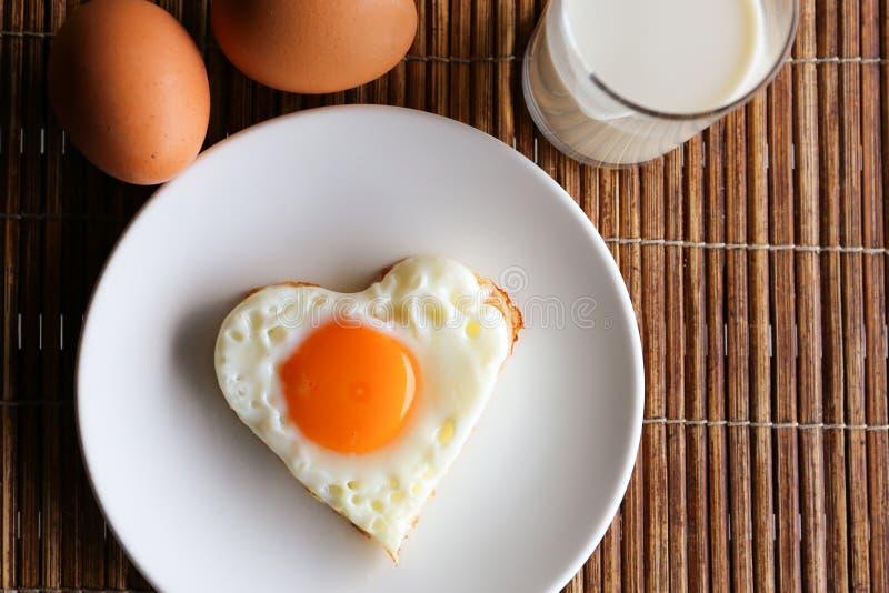 Huevo frito en forma del corazón y la opinión superior de la leche fotos de archivo