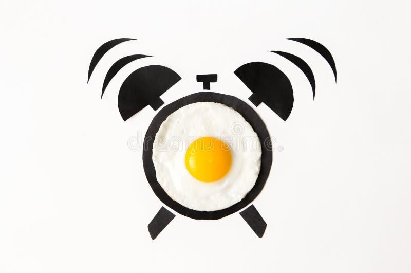 Huevo frito en la forma del despertador, concepto del tiempo de desayuno imagenes de archivo