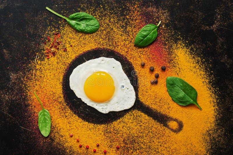 Huevo frito en la silueta de la cacerola de la especia, fondo oscuro, endecha plana El concepto de comida imagenes de archivo